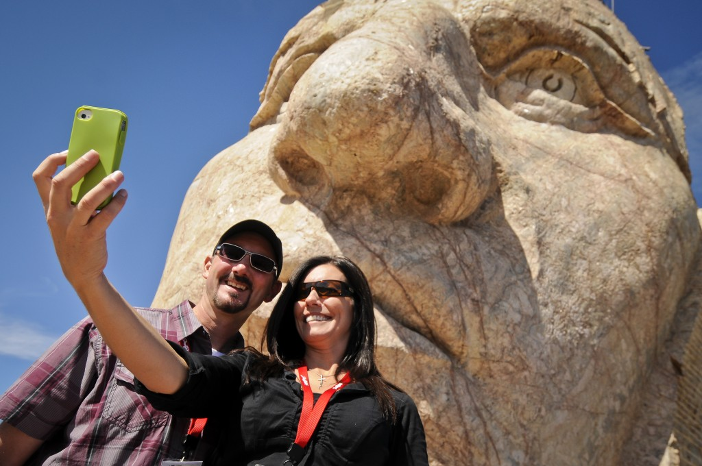A couple takes a selfie under the face of the Crazy Horse.